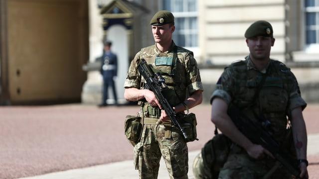 Purtret dal Buckingham Palace e schuldads armads ch'èn postads davantvart.