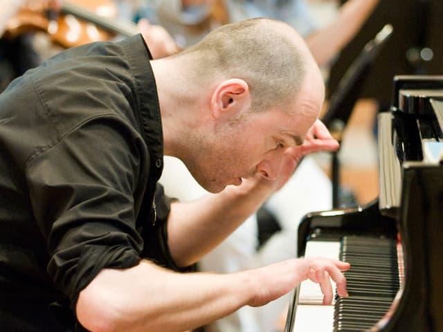 Ein Mann spielt konzentriert Klavier.