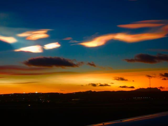 Über dem Abendrot und dunklen Quellwolken sind die hellen, farbigen Stratosphärenwolken zu sehen.