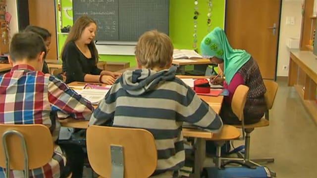 Schülerin mit Kopftuch inmitten anderer Schüler.