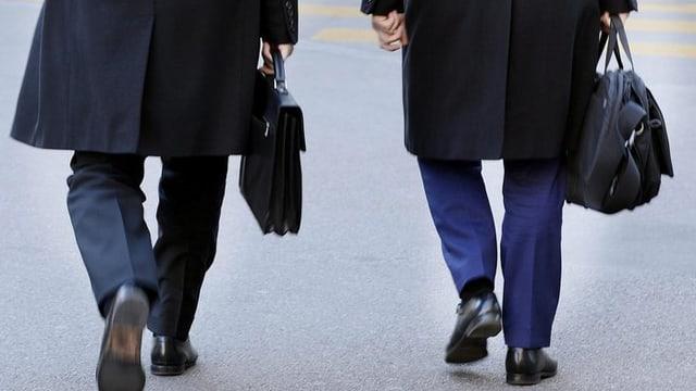Zwei Männer laufen mit einer Aktentasche auf dem Zürcher Paradeplatz.