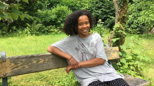 Eine schwarze Frau sitzt auf einer Bank und blickt in die Kamera.