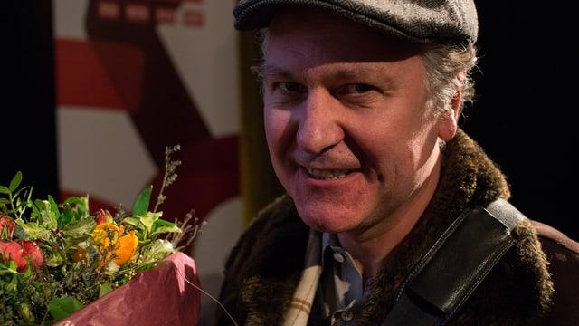 Der Preisträger Peter Volkart, mit Blumenstrauss.