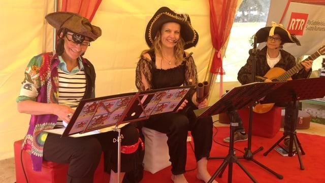 La ghitarrista Jacinta Jacomet cun las raquintadras Sandra Carisch e Marionna Lombriser.