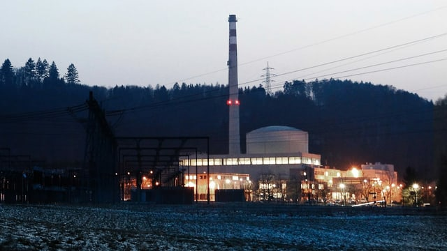 Zu sehen ist das Kernkraftwerk Mühleberg in der Dämmerung. Die Fenster sind hell erleuchtet.