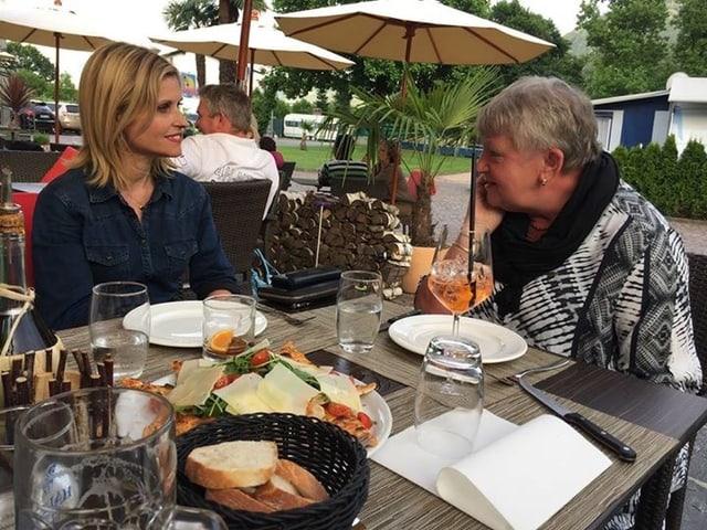 zwei Frauen sitzen an einem gedeckten Tisch und reden miteinander.