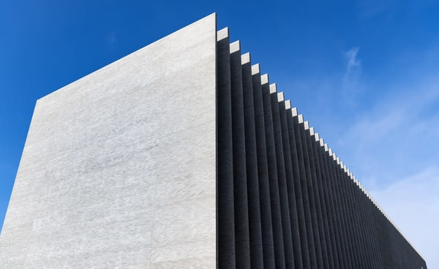 Ein Betonbau mit Lamellen vor blauem Himmel