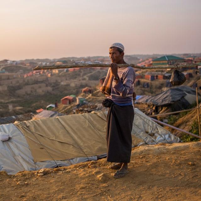 Ein Rohingya hält einen Beutel an einem Stock.
