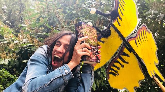 Annette König hält das Buch «Die Tyrannei des Schmetterlings» als Schutzschild gegen ein Insekt
