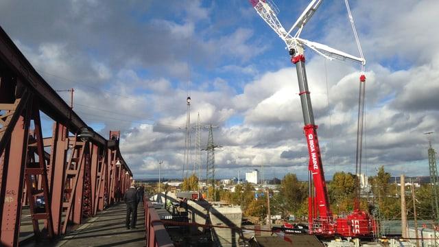 Der rot-weisse Kran neben der besetehenden Autobrücke.