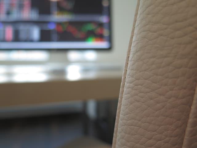 Leerer Sitzplatz vor Computer-Bildschirm des Börsenhändlers