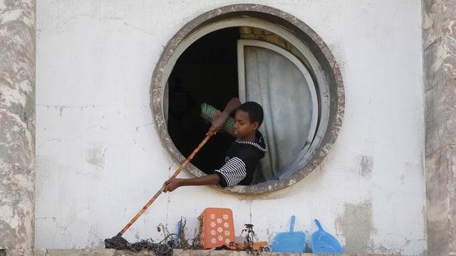 Ein Junge beim Hausputz.