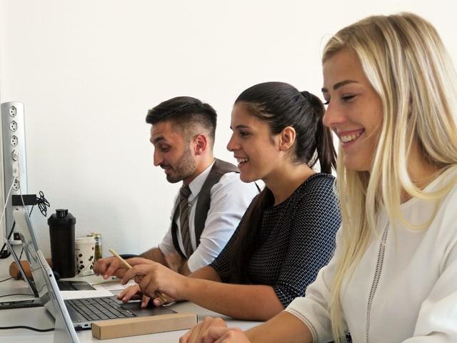 Drei junge Leute in einem Schulzimmer beim Lernen am Computer.