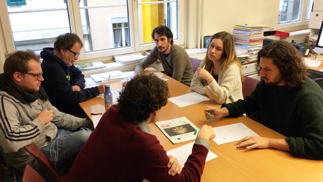 Fünf Männer und eine Frau sitzen diskutieren an einem Bürotisch.