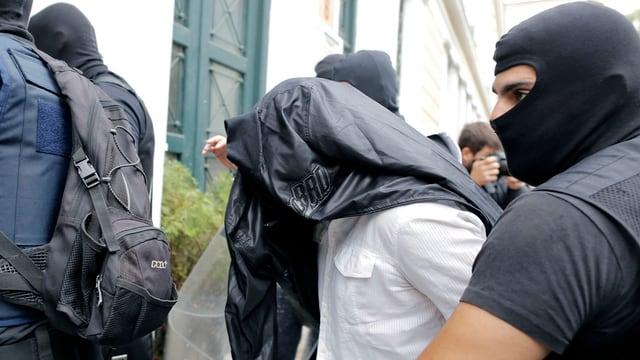 Vermummte Polizisten mit einem Festgenommenen.