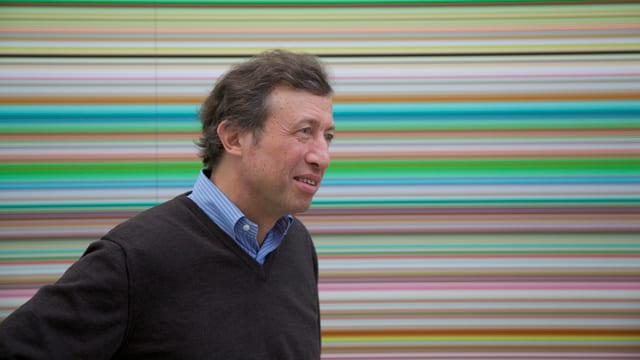 Ein Mann mit blauem Hemd und schwarzem Pullover vor einem Bild mit vielen schmalen, farbigen horizontalen Streifen.
