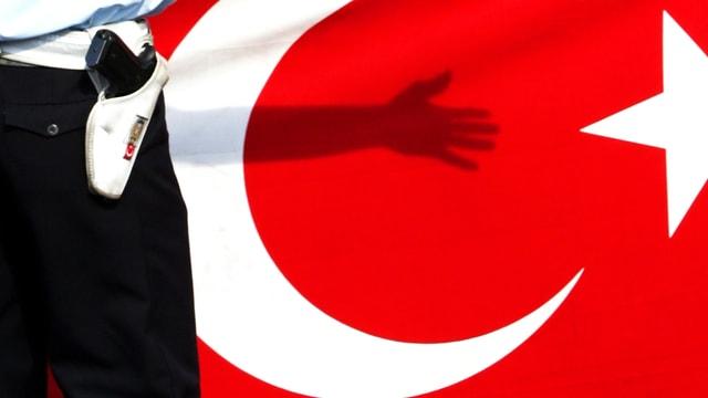 Ein Polizist steht vor einer Türkei-Flagge, dahinter der Schatten eines Armes. (reuters)