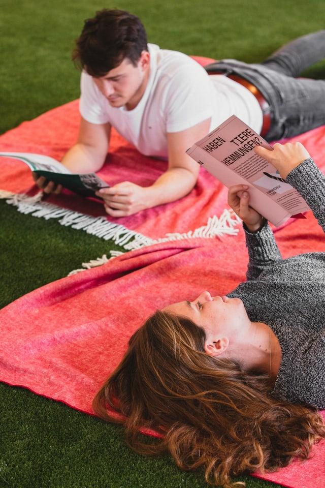 Paar liegt auf Kunstrasen und liest Zeitung