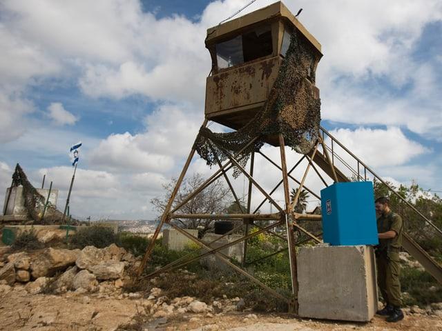 Ein Soldat gibt in einer improvisierten Wahlkabine auf einer Mauer an einem Posten in der Westbank seine Stimme ab, im Hintergrund ein Wachturm
