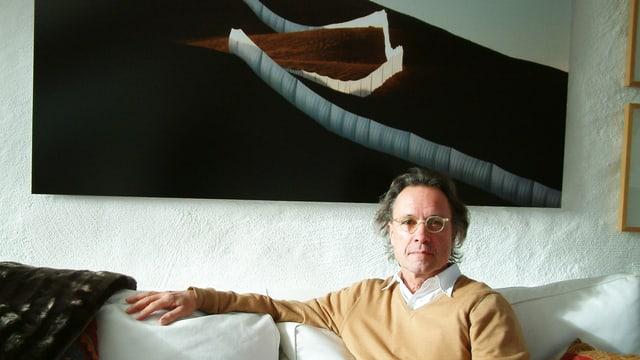 Wolfgang Volz vor einem Foto, das einen Zaun aus Tüchern zeigt.