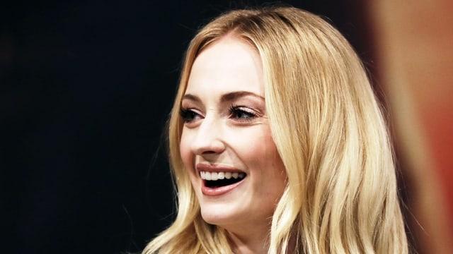 Blonde Frau blickt lachend zur Seite.