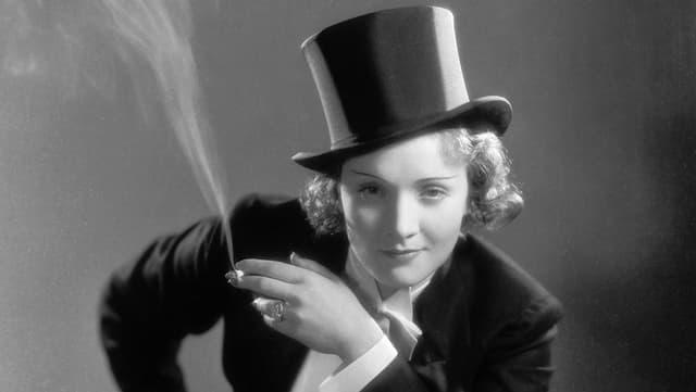 Marlene Dietrich im Anzug mit Zylinder und Zigarette.