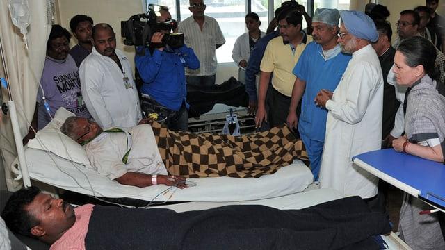 Premierminister Manmohan Singh an einem Krankenbett.