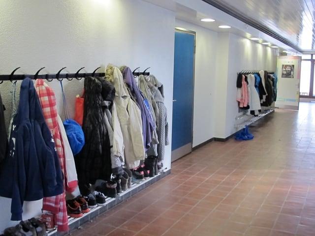 Ein Korridor in einem Schulhaus mit Schülerjacken an der Garderobe.
