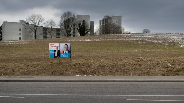 Ein FDP-Wahlplakat vor grauem Himmel und grauen Wohnblöcken auf einer kargen Wiese.