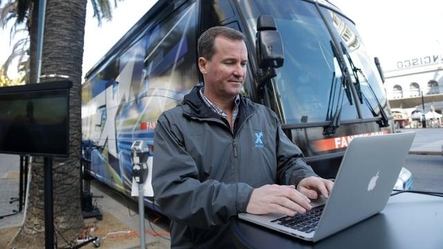 Fantex-CEO Buck French an einem Laptop vor einem Reisecar.