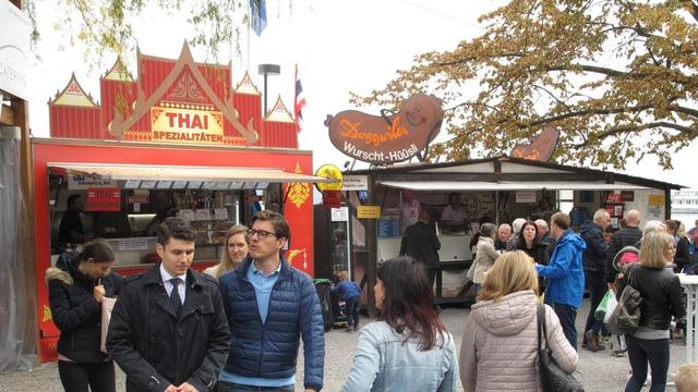 Leute an einem Jahrmarkt vor einem Essstand der Thai-Küche anbietet.