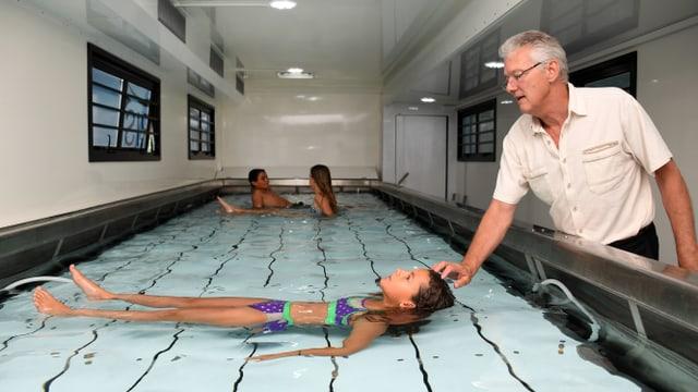 Il scolast gida ina scolara en il bassin dal bogn mobil.