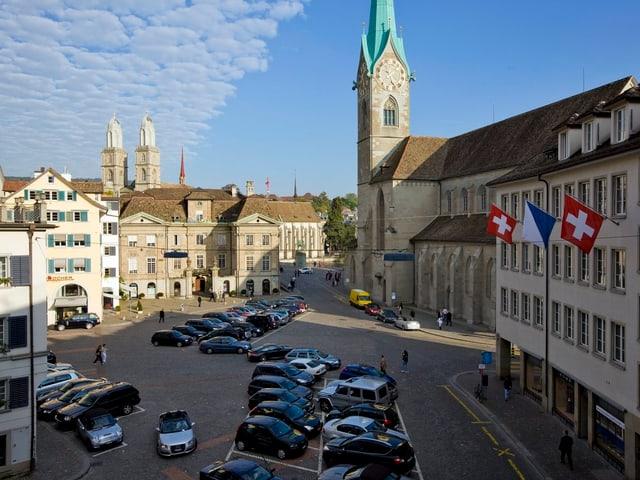 Der Platz «Münsterhof» unter blauem Himmel mit zahlreichen parkierten Autos.