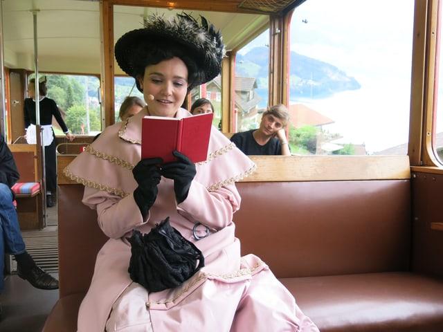 Mrs. Fleming sitzt in der Zahnradbahn und liest.