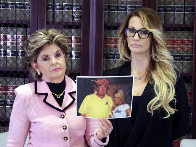 Jessica Drake und ihre Anwältin, welche ein Foto von Drake und Trump in der Hand hält.