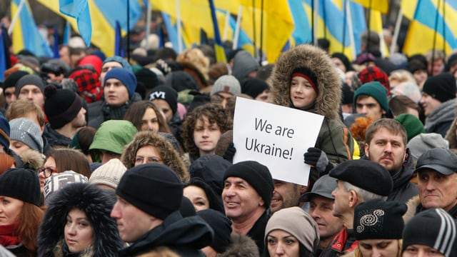 Ucranais che commemoreschan ed in buob che tegna si in placat cun «Nus essan Ucraina».