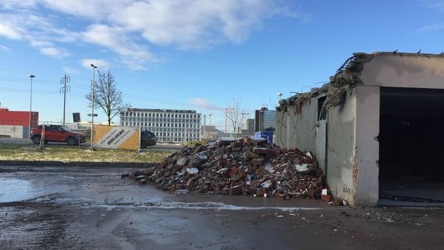Ein halb abgerissenes Haus, davor liegt ein Haufen Bauschutt.