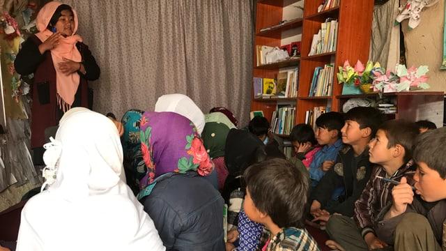 Jung Frau steht in einem Raum. Vor ihr sitzen Buben und Mädchen mit Kopftüchern.