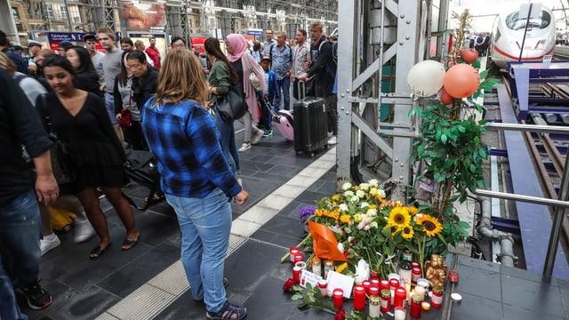Bahnhofhalle mit Geleisen. Daneben eine Gedenkstätte mit Blumen und Trauerkerzen.