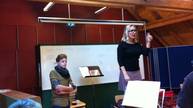 Eine Frau dirigiert, daneben steht ein Junge.