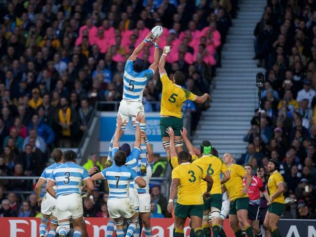 Ein argentinischer und ein ein australischer Spieler werden hochgehoben und kämpfen um den Ball.