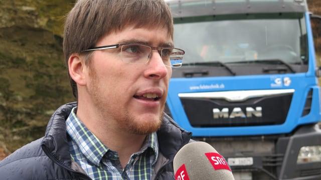 Mann spricht in SRF-Mikrofon vor grossem Lastwagen