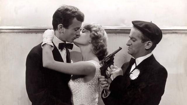 Ein Paar küsst sich neben einem Mann, der eine Pistole gegen sich richtet.