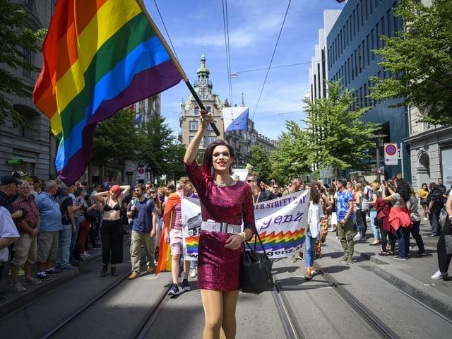 Eine Dragqueen oder Transfrau in einem glitzernden Kleid läuft an der Zürich Pride mit und schwingt dabei eine Regenbogenfahne.