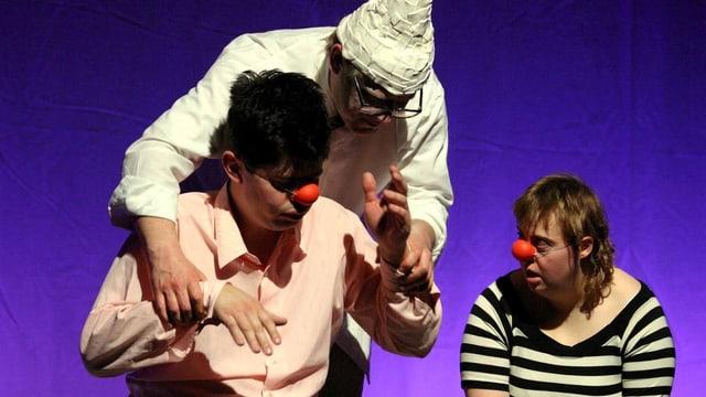 Zwei Männer und eine Frau mit roten Nasen auf einer Bühne