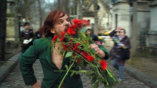 Ein Mann mit langen Haaren rennt durch einen Friedhof. Er hält einen Blumenstrauss in der Hand und scheint diesen zu essen.