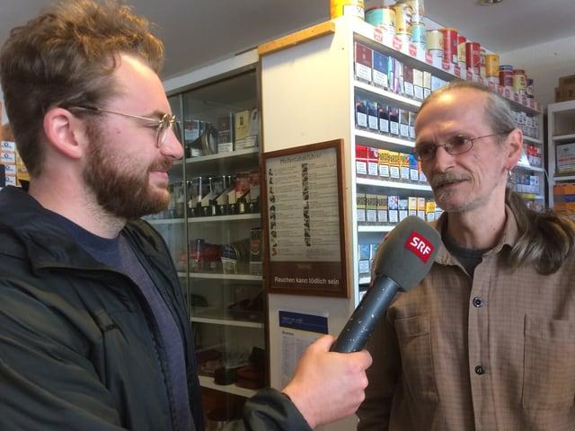 Zwei Männer während eines Radiointerviews in einem Kiosk.