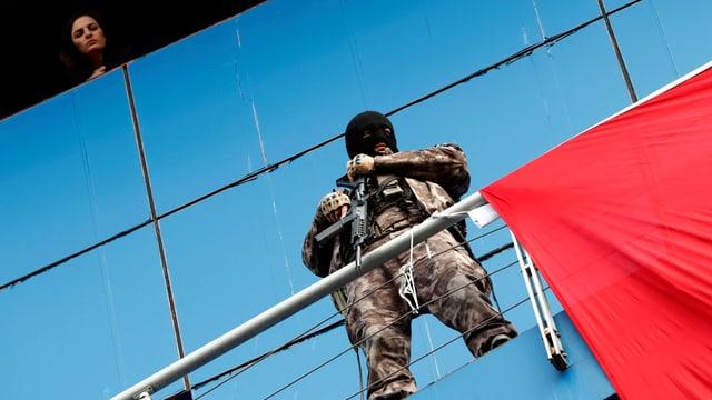 Ein vermummter und bewaffneter Polizist steht in einem Tarnanzug vor einer Hausfassade und blickt hinunter.