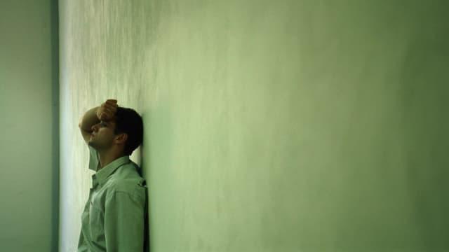 Mann, der sich bedrückt an die Wand lehnt.