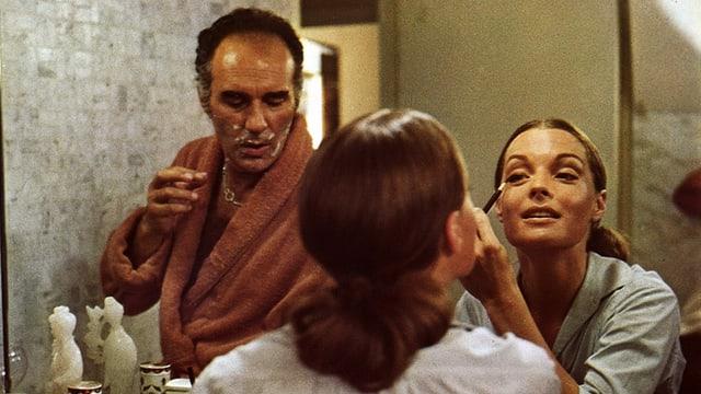 Ein Mann und eine Frau vor dem Spiegel. Sie schminkt sich.